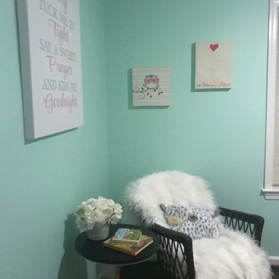 white fuzzy chair in teal room